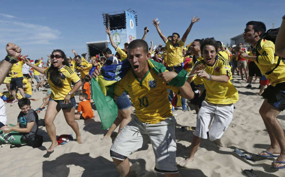 Colombia soccer fans celebrate their team's goal against Greece as they watch the World Cup game inside the FIFA Fan Fest area on Copacabana beach in Rio de Janeiro, Brazil, Saturday, June 14, 2014. (AP Photo/Silvia Izquierdo)