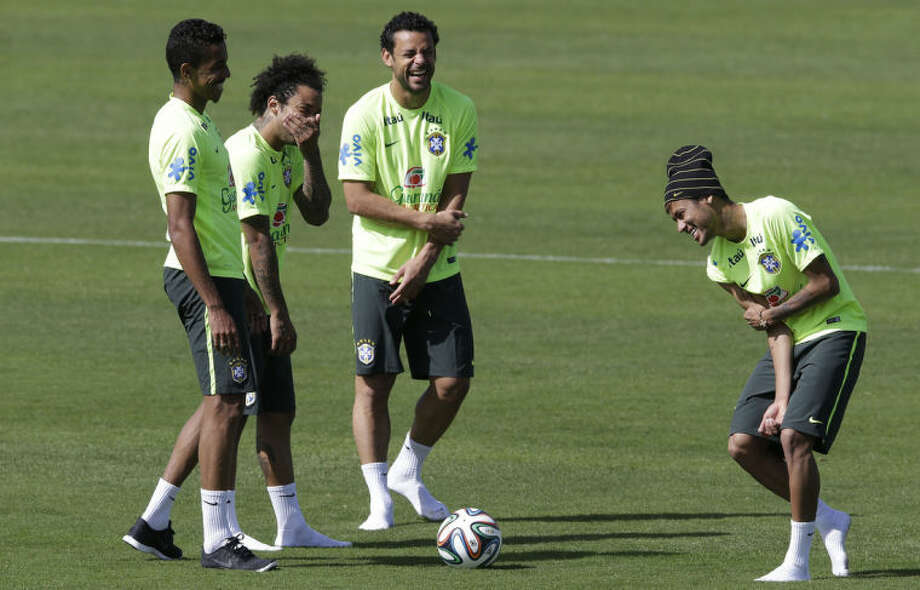 Brazil's Neymar, right, Fred, second from right, Luiz Gustavo, left, and Marcelo, joke during a training session at the Granja Comary training center in Teresopolis, Brazil, Saturday, June 14, 2014. Brazil plays in group A at the 2014 soccer World Cup. (AP Photo/Andre Penner)