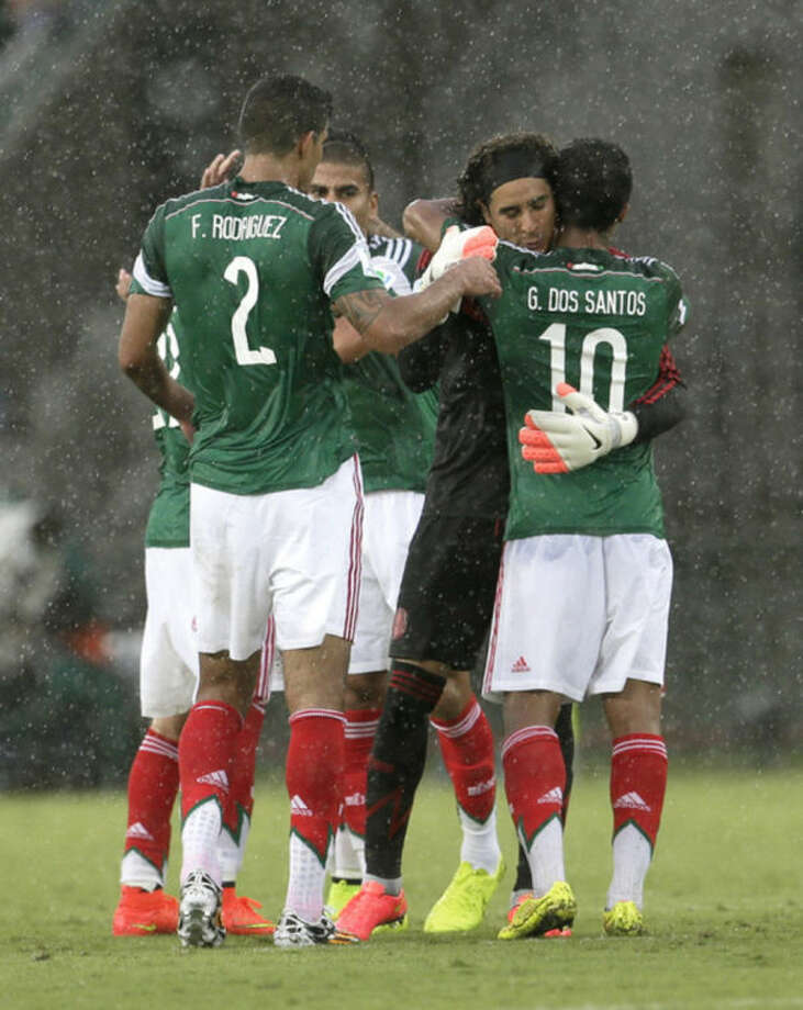 Mexico's Francisco Rodriguez (2) and Giovani dos Santos (10) congratulate their goalkeeper Guillermo Ochoa following their 1-0 victory over Cameroon in the group A World Cup soccer match between Mexico and Cameroon in the Arena das Dunas in Natal, Brazil, Friday, June 13, 2014. (AP Photo/Petr David Josek)