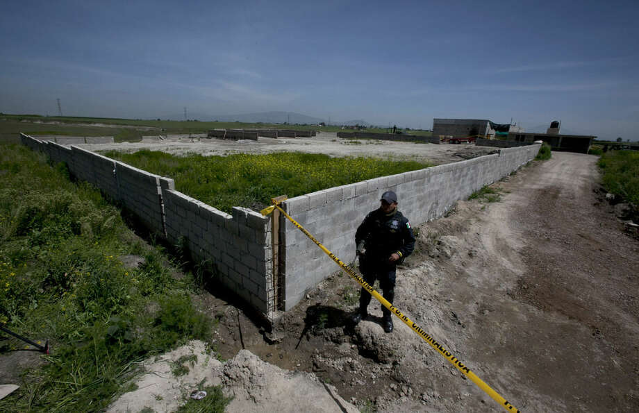 """A Federal Police officer stands guard on the perimeters of a half-built house near the Altiplano maximum security prison in Almoloya, west of Mexico City, Monday, July 13, 2015. A widespread manhunt that included highway checkpoints, stepped up border security and closure of an international airport failed to turn up any trace of Mexican drug kingpin Joaquin """"El Chapo"""" Guzman by Monday, more than 24 hours after he escaped through an underground tunnel in his Altiplano prison cell. (AP Photo/Marco Ugarte)"""