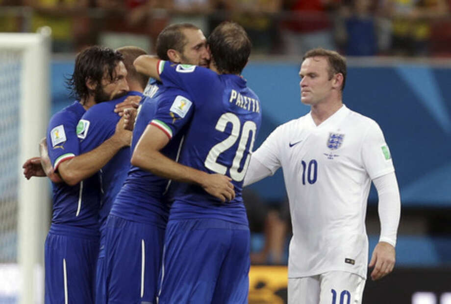 England's Wayne Rooney, right, looks on as Italy's Gabriel Paletta, center, and other Italian players celebrate after the group D World Cup soccer match between England and Italy at the Arena da Amazonia in Manaus, Brazil, Saturday, June 14, 2014. Italy won the match 2-1. (AP Photo/Martin Mejia)