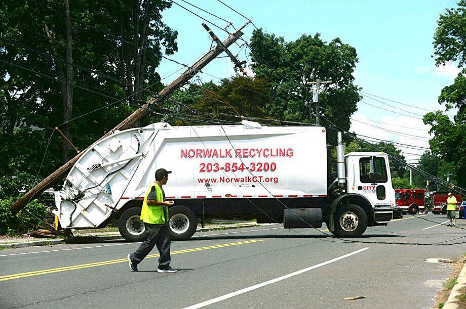 Hour photo/Erik TrautmanA City Carting truck snapped a utility Poole closing Ward St in Norwalk Friday morning.