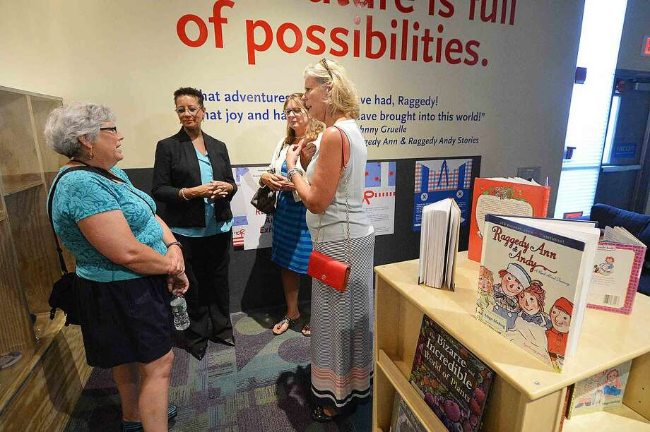 Norwalk Historical Society Executive Director Diane Jellerette, center, talks with other members during an opening reception at Stepping Stones Museum for Children for Raggedy Ann, Native of Norwalk exhibit.