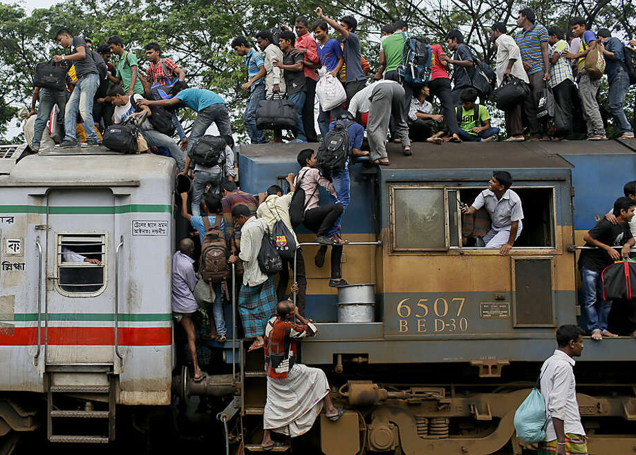Bangladeshi Muslims try to climb on to the roof of an overcrowded train as they head to their homes ahead of Eid al-Fitr at a railway station in Dhaka, Bangladesh, Thursday, July 16, 2015. Hundreds of thousands of people working in Dhaka plan to leave for their home towns to celebrate with their family the upcoming Eid al-Fitr. (AP Photo/A.M. Ahad)