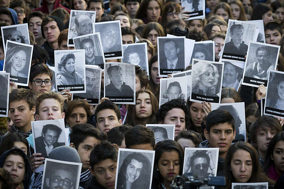 People hold up pictures of the victims from the AMIA Jewish community center bombing on the 21st anniversary of the terror attack in Buenos Aires, Argentina, Friday, July 17, 2015. The bombing of the Argentine-Israeli Mutual Association in downtown Buenos Aires killed 85 people in 1994 and remains unsolved. (AP Photo/Victor R. Caivano)