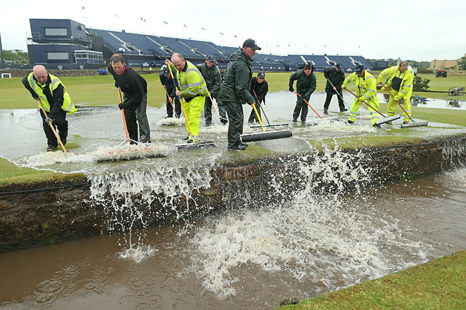 Ground staff sweep flood water into the Swilcan Burn after heavy rain delayed the start of the second round of the British Open Golf Championship at the Old Course, St. Andrews, Scotland, Friday, July 17, 2015. (AP Photo/Peter Morrison)