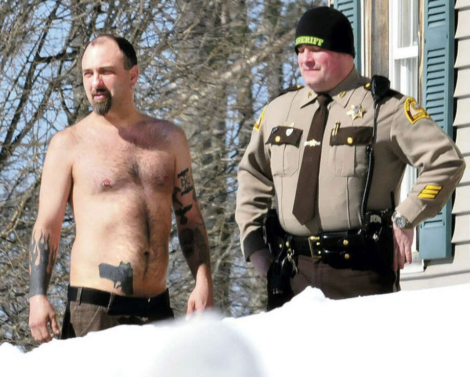 FILE - In this March 18, 2014 file photo, Michael Smith, left, bearing a realistic-looking tattoo of a handgun on his stomach, stands beside a Somerset County Sheriff deputy outside his home in Norridgewock, Maine. Smith was arrested Friday, June 13, 2014, after he allegedly showed up at a deputy's home with a real gun in his waistband and drugs in his backpack. He was charged with stealing prescription narcotics from his girlfriend and released from the Somerset County Jail on $1,000 cash bail. It's not known if he has a lawyer. (AP Photo/Morning Sentinel, David Leaming, File)