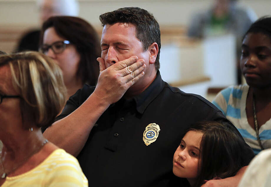 Chuck Hartung holds his daughter Haley, 8, during a prayer service at Wesley Memorial United Methodist Church for the victims of shootings at a recruiting center and another U.S. military site a few miles apart in Chattanooga, Tenn., Thursday, July 16, 2015. Federal authorities said they were investigating the possibility it was an act of terrorism, and the FBI took charge of the case. (AP Photo/John Bazemore)