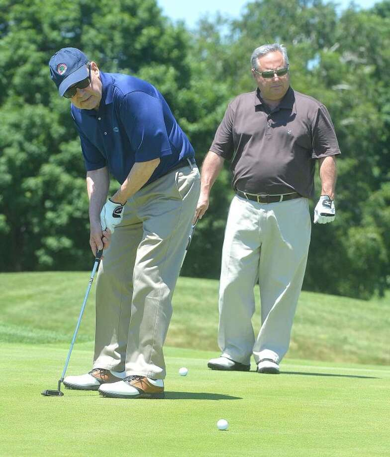 Hour Photo/Alex von Kleydorff Joe Kendy puts as Tony Aitoro watches during the Greater Norwalk Chamber of Commerce Golf Classic at Shorehaven Country Club on Monday