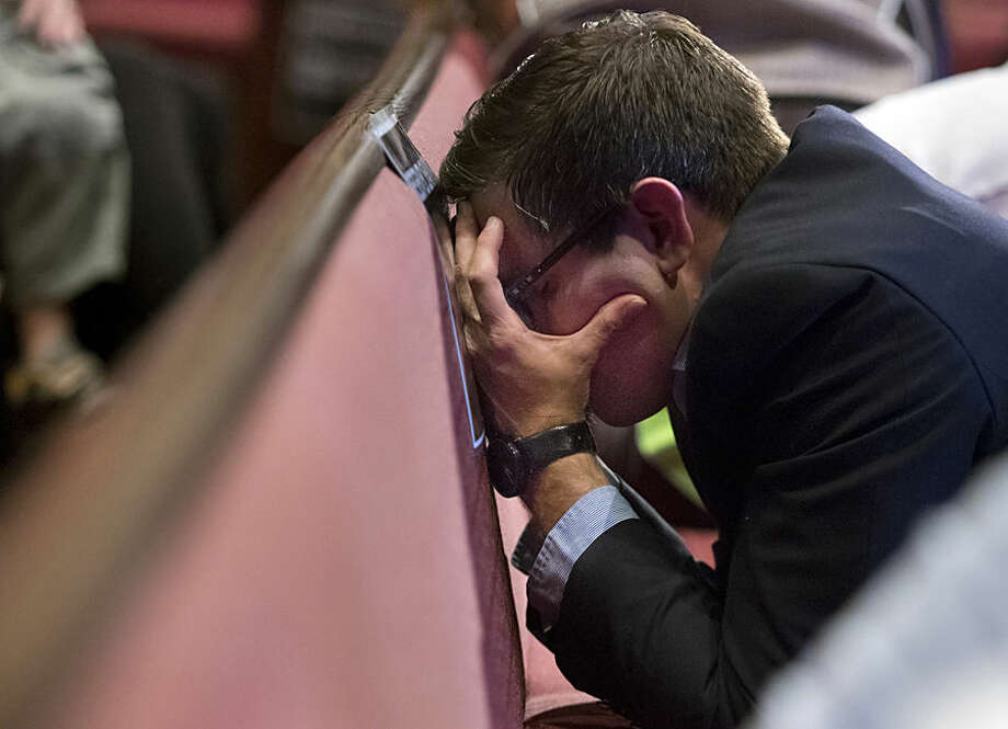 Chad Harris puts his face against a pew as he prays during a prayer vigil at Redemption Point Church for the victims of shootings at a recruiting center and another U.S. military site a few miles apart in Chattanooga, Tenn., Thursday, July 16, 2015. Federal authorities said they were investigating the possibility it was an act of terrorism, and the FBI took charge of the case. (Doug Strickland/Chattanooga Times Free Press via AP) THE DAILY CITIZEN OUT; NOOGA.COM OUT; CLEVELAND DAILY BANNER OUT; LOCAL INTERNET OUT; MANDATORY CREDIT