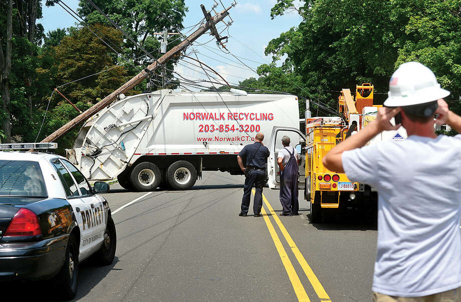 Hour photo / Erik TrautmannA City Carting refuse truck snapped a utility pole closing Ward St in Norwalk Friday monrning.