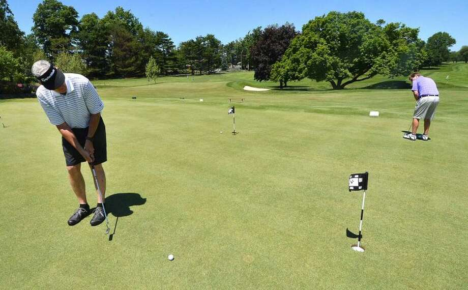 Hour Photo/Alex von Kleydorff Chamber Chairman of the Board Mike Sutton warms up by sinking some long shots on the putting green during the Greater Norwalk Chamber of Commerce Golf Outing at Shorehaven Country Club on Monday