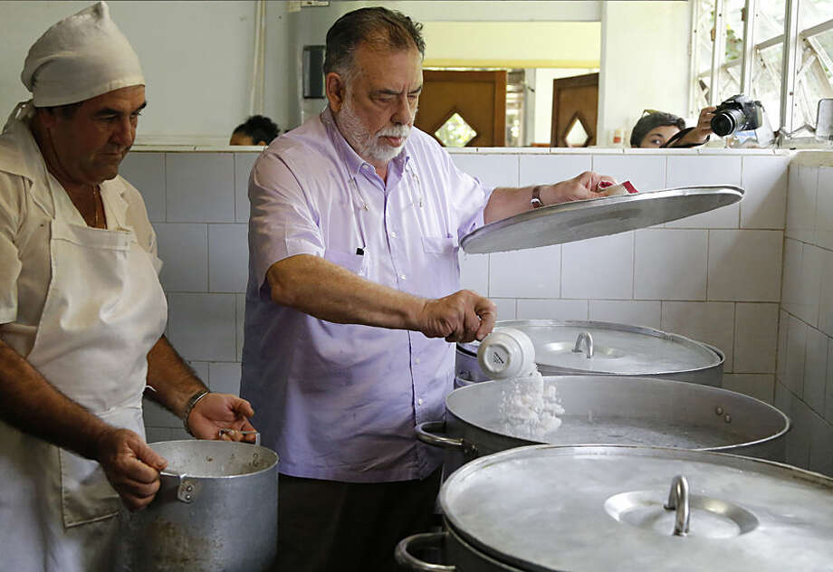 American film director Francis Ford Coppola adds salt to boiling water in the kitchen of the International School of Film and Television in San Antonio de Los Banos, near Havana, Cuba, Thursday, July 16, 2015. Coppola who is on a visit to Cuba, met and interacted with students at the school, and prepared a pasta meal for the students. (AP Photo/Desmond Boylan)