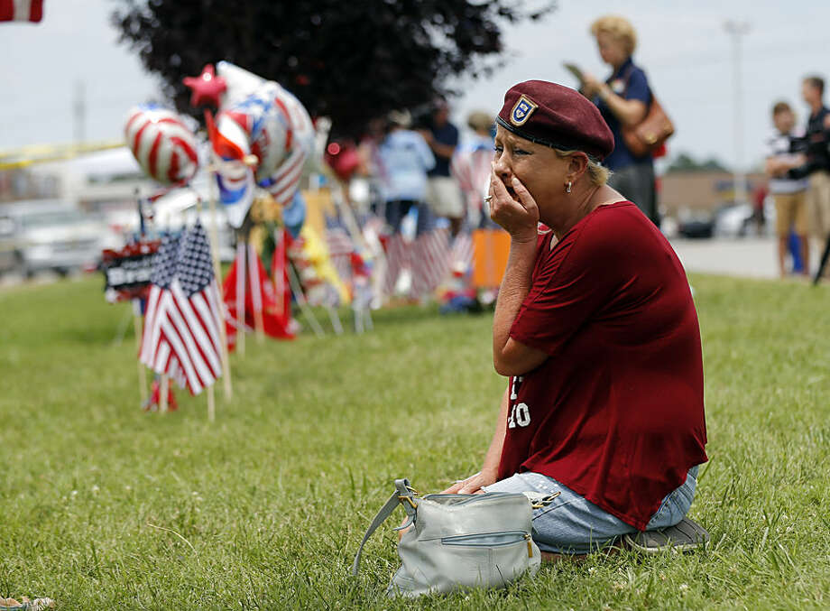 Laurie Norman becomes emotional as she looks at a makeshift memorial outside a military recruiting center Friday, July 17, 2015, where a gunman opened fire Thursday in Chattanooga, Tenn. Counterterrorism investigators are trying to figure out why a 24-year-old Kuwait-born man, who by accounts lived a typical life in suburban America, attacked the career center and a Navy-Marine training center a few miles away in a shooting rampage that killed four Marines. (AP Photo/Mark Zaleski)