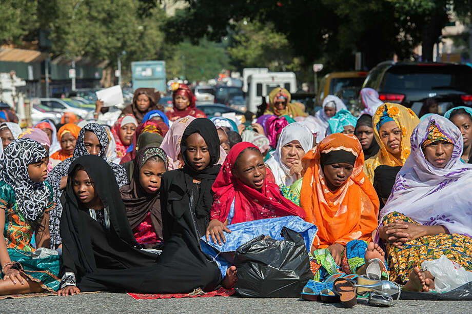 Women and girls in New York's East Harlem neighborhood take part in the traditional annual prayer commemorating the end of Ramadan in front of the Masjid Aqsa-Salam mosque on Friday, July 17, 2015. The Islamic Eid Al-Fitr holiday celebrates the conclusion of 30 days of dawn-to-sunset fasting. (AP Photo/Bryan R. Smith)