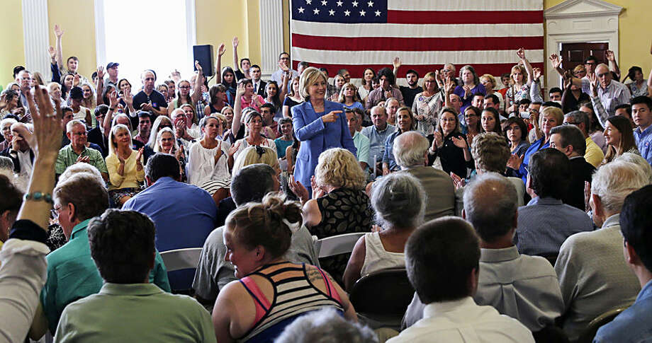Audience guests raise their hands to ask a question to Democratic presidential candidate Hillary Rodham Clinton as she addresses a gathering during a town hall meeting in Dover, NH, Thursday, July 16, 2015. (AP Photo/Charles Krupa)