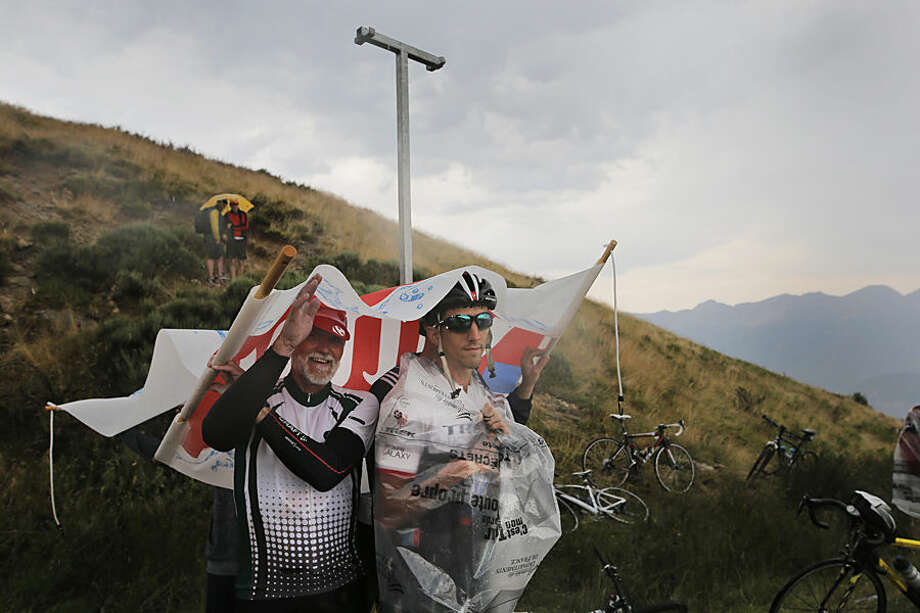 Two spectators, one covered with a plastic garbage bag, take cover from the rain under a publicity banner during the twelfth stage of the Tour de France cycling race over 195 kilometers (121.2 miles) with start in Lannemezan and finish in Plateau de Beille, France, Thursday, July 16, 2015. (AP Photo/Laurent Cipriani)