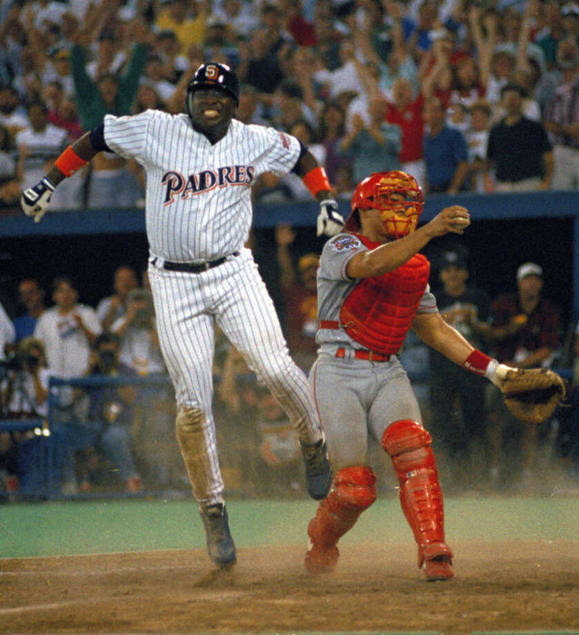FILE - In this July 12, 1994 file photo, San Diego Padres' Tony Gwynn leaps in the air after sliding home safely to score the winning run as Texas Rangers catcher Ivan Rodriguez stands by in the 10th inning of the MLB All-Star Game at Pittsburgh's Three Rivers Stadium. The Baseball Hall of Fame said Gwynn died of cancer on Monday, June 16, 2014. He was 54. (AP Photo/Carlos Osorio, File)
