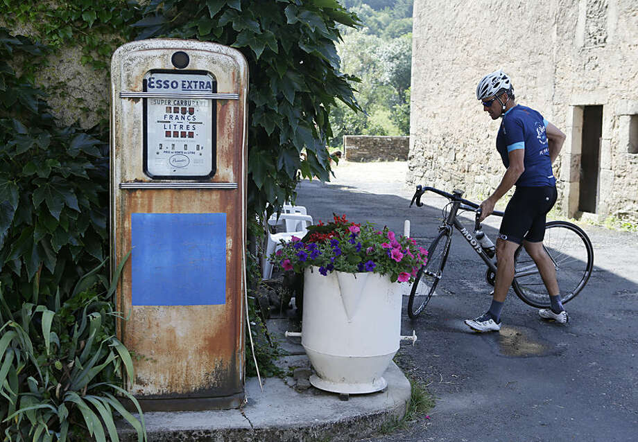"""Lance Armstrong parks his bike in Bouloc, during the charity ride """"Le Tour, One Day Ahead,"""" between Rodez and Mende, southern France, Friday July 17, 2015. While the Tour de France is going on, Armstrong takes part to a charity ride called """"Le tour-One Day Ahead"""" with the goal of raising money to cure Leukemia. (AP Photo/Lionel Cironneau)"""