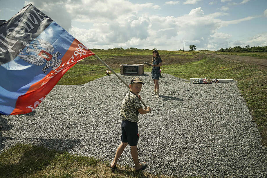 A boy waves a flag of the self-proclaimed Donetsk People's Republic at a memorial to the victims of the Malaysian Airlines MH17 plane crash at the crash site near the village of Hrabove, eastern Ukraine, Thursday, July 16, 2015. A year since a Malaysia Airlines Boeing 777 was blown out of the sky over war-ravaged eastern Ukraine, killing 298 people, there has been little official word of progress in determining what brought down Flight MH17. (AP Photo/Mstyslav Chernov)