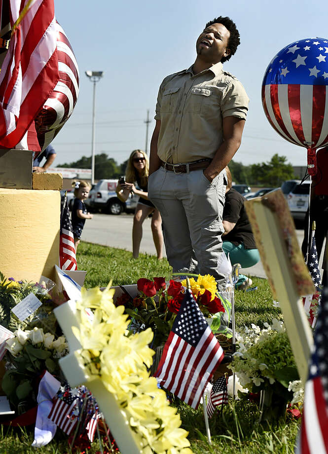 """Michael Dexter sings """"Amazing Grace"""" by a makeshift memorial outside the Armed Forces Career Center on Friday, July 17, 2015, in Chattanooga, Tenn. Counterterrorism investigators are trying to figure out why a 24-year-old Kuwait-born man, who by accounts lived a typical life in suburban America, attacked the career center and a Navy-Marine training center a few miles away in a shooting rampage that killed four Marines. (AP Photo/Mark Zaleski)"""