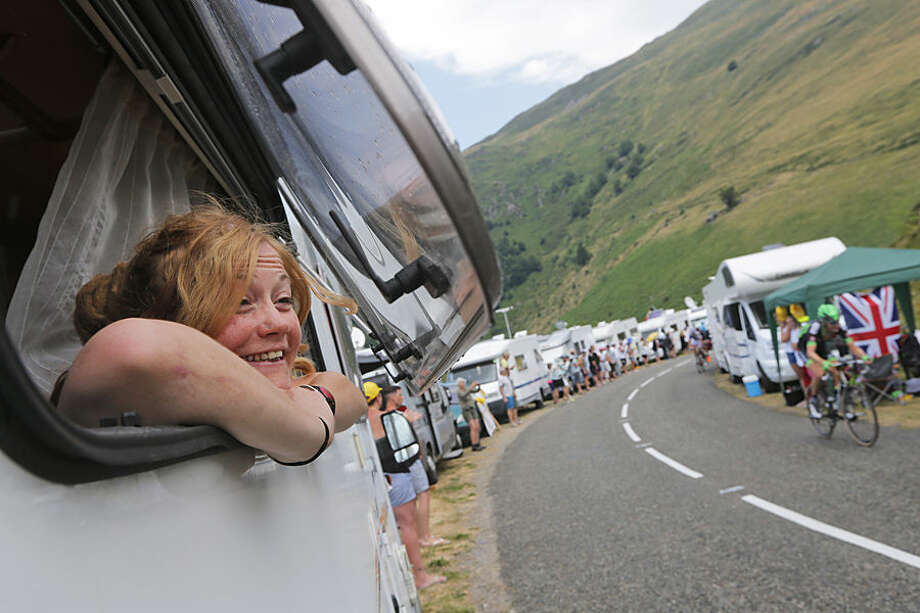 A woman watches the riders pass from the window of a camping car during the twelfth stage of the Tour de France cycling race over 195 kilometers (121.2 miles) with start in Lannemezan and finish in Plateau de Beille, France, Thursday, July 16, 2015. (AP Photo/Christophe Ena)