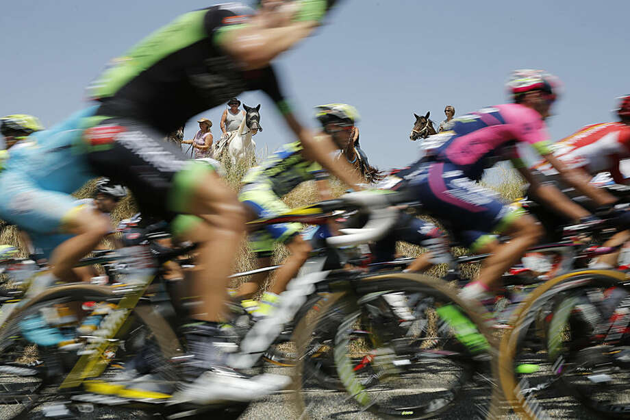 Riders on horseback watch the pack pass during the thirteenth stage of the Tour de France cycling race over 198.5 kilometers (123.3 miles) with start in Muret and finish in Rodez, France, Friday, July 17, 2015. (AP Photo/Laurent Cipriani)