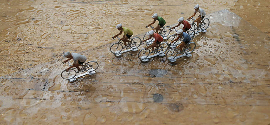 Miniature riders sit on a rain covered table in the media zone behind the finish line after the twelfth stage of the Tour de France cycling race over 195 kilometers (121.2 miles) with start in Lannemezan and finish in Plateau de Beille, France, Thursday, July 16, 2015. (AP Photo/Laurent Cipriani)