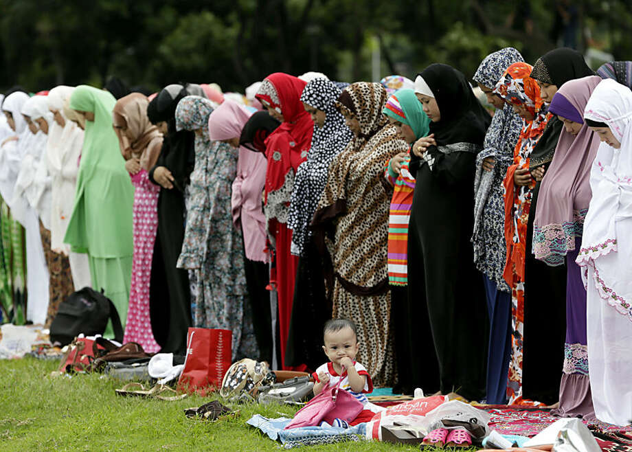 A baby girl sits by herself as Filipino Muslims pray at Rizal Park to mark the end of the holy month of Ramadan known as Eid al-Fitr Friday, July 17, 2015 in Manila, Philippines. Muslims all over the world mark the celebration of Eid with prayers, festivities and family reunions. (AP Photo/Bullit Marquez)