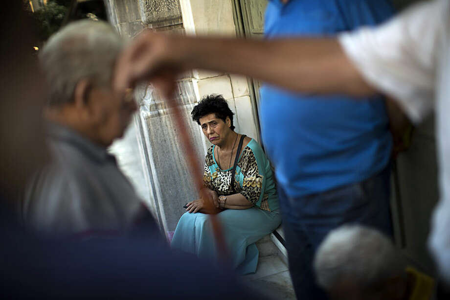 Pensioners wait for the opening of the national bank of Greece to withdraw a maximum of 120 euros ($134) for the week in central Athens, Thursday, July 16, 2015. Greece's troubled left-wing government is seeking urgent relief from European lenders on Thursday, after it pushed a harsh austerity package thought parliament, triggering a revolt in the ruling party and violent demonstrations in central Athens. (AP Photo/Emilio Morenatti)