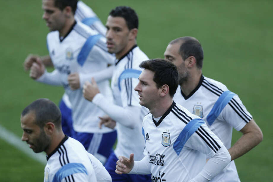 Argentina's Lionel Messi, center, jogs with teammates during a training session in Vespasiano, near Belo Horizonte, Brazil, Monday, June 16, 2014. Argentina plays in group F of the 2014 soccer World Cup. (AP Photo/Victor R. Caivano)