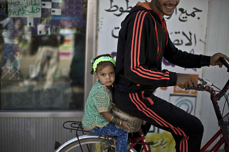 A Syrian man and his daughter ride a bicycle while celebrating the first day of the Eid al-Fitr holiday that marks the end of the holy fasting month of Ramadan at Zaatari refugee camp, in Mafraq, Jordan, Friday, July 17, 2015. (AP Photo/Muhammed Muheisen)