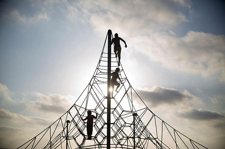 Children climb at a playground next to the Mediterranean Sea during the first day of the Eid al-Fitr holiday as the sun sets in Tel Aviv, Israel, Friday, July 17, 2015. The three-day holiday marks the end of the holy fasting month of Ramadan. (AP Photo/Ariel Schalit)