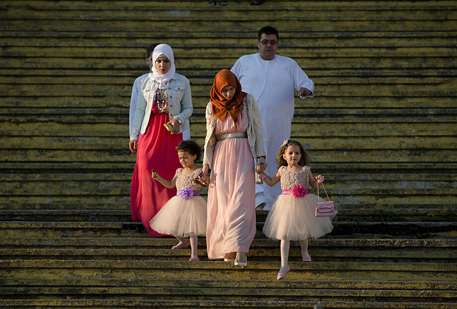 A Muslim family arrives for the Eid al-Fitr prayers in Bucharest, Romania, Friday, July 17, 2015. Members of the Romania Muslim community joined prayers at the Dinamo stadium in the Romanian capital, in the largest Muslim public gathering of the year. Eid al-Fitr marks the end of the holy fasting month of Ramadan. (AP Photo/Vadim Ghirda)
