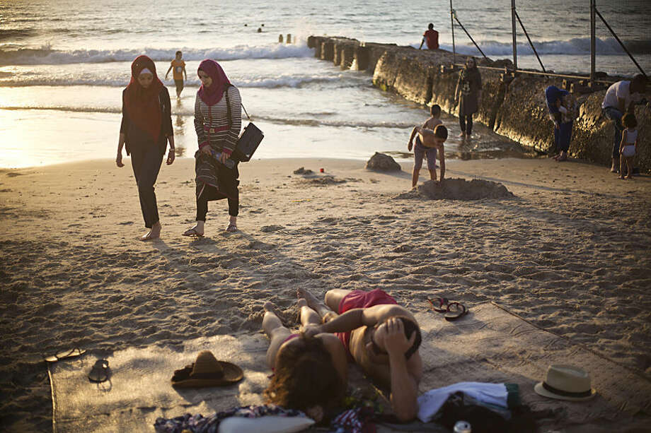 Muslim women stroll after bathing in the Mediterranean sea during the first day of the Eid al-Fitr holiday as the sun sets in Tel Aviv, Israel, Friday, July 17, 2015. The three-day holiday marks the end of the holy fasting month of Ramadan. (AP Photo/Ariel Schalit)