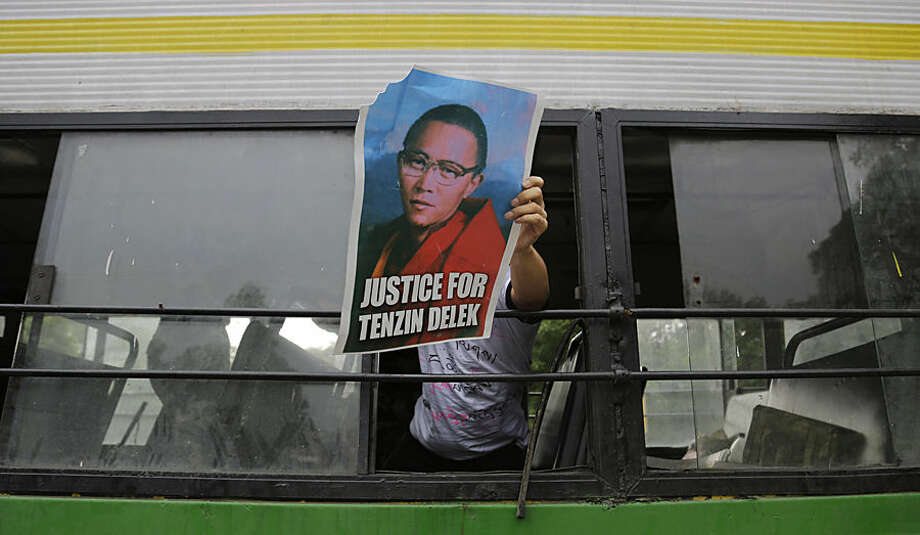 A Tibetan exile displays a portrait of Tibetan lama Tenzin Delek Rinpoche, 65, who passed away in custody in a Chinese prison on July 12, from inside a bus after being detained outside the Chinese embassy during a protest in New Delhi, India, Friday, July 17, 2015. Chinese authorities cremated the body of the Tibetan lama in a prison Thursday against the wishes of his family, who had wanted to perform Buddhist funeral rites on the body in his hometown, a rights group said. (AP Photo/Altaf Qadri)