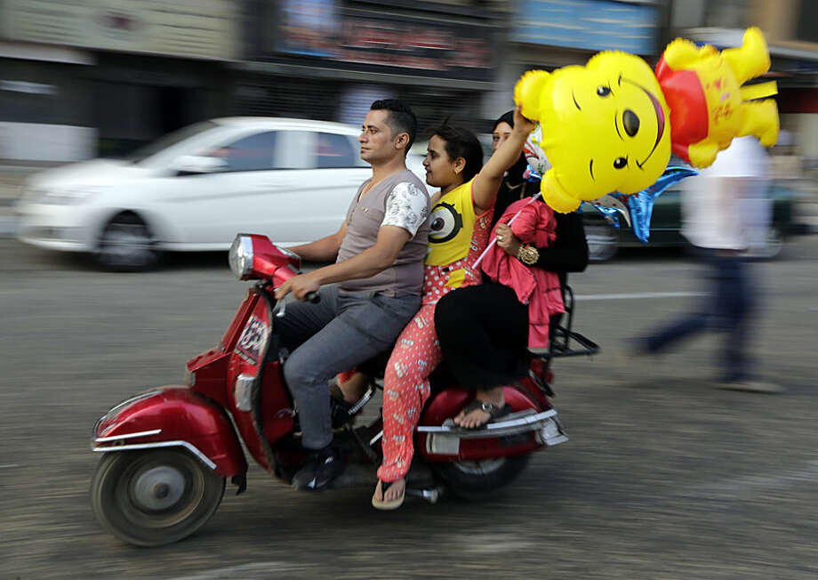 Egyptians ride a motorbike as they celebrate Eid al-Fitr feast, marking the end of the Muslim fasting month of Ramadan in Cairo, Egypt, Friday, July 17, 2015. (AP Photo/Amr Nabil)