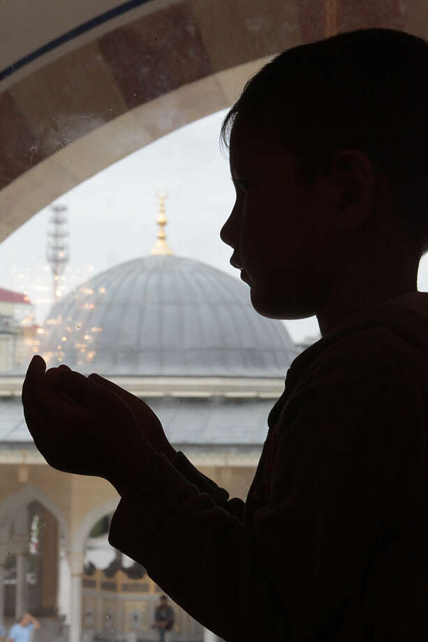 A Chechen boy performs an Eid al-Fitr prayer to mark the end of the holy fasting month of Ramadan in Chechen capital of Grozny, Russia, Friday, July 17, 2015. Eid al-Fitr prayer marks the end of the holy fasting month of Ramadan. (AP Photo/Musa Sadulayev)