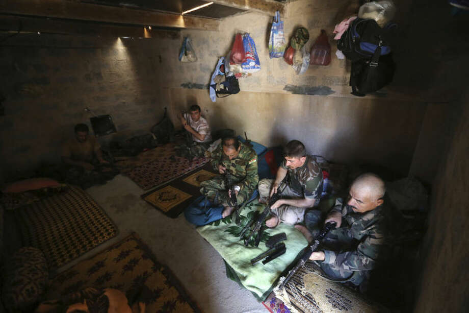 """Kurdish peshmerga fighters clean their weapons at a base on the closet front line with militants from the al-Qaida-inspired Islamic State in Iraq and the Levant (ISIL), in Tuz Khormato, 100 kilometers (62 miles) south of the oil rich province of Kirkuk, northern Iraq, Wednesday, June 25, 2014. A defiant Prime Minister Nouri al-Maliki rejected calls Wednesday for an interim """"national salvation government"""" intended to undermine the Sunni insurgency by presenting a unified front among Iraq's three main groups, calling it a """"coup against the constitution."""" (AP Photo/Hussein Malla)"""
