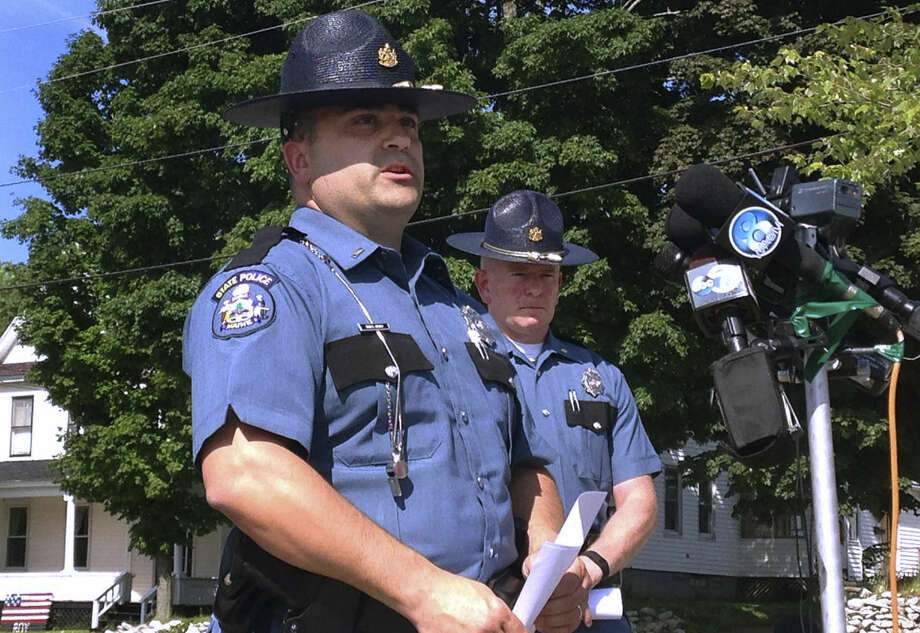 Maine State Police Lt. Sean Hashey, left, speaks Friday, July 17, 2015, outside the police department in Lincoln, Maine. Suspect Anthony Lord was arrested without incident Friday at a family member's home in Houlton, Maine, and faces charges in the shootings of several people overnight several towns in northern Maine. At right is State Police Maj. Chris Grotton. (AP Photo/Alanna Durkin)