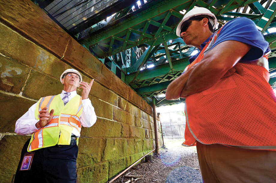 Hour photo / Erik Trautmann Metro-North Railroad and CT DOT officials including CT DOT commissioner Jim Redecker, left, give local media a tour of the inner workings of the 118-year-old Walk train bridge in Norwalk Wednesday.