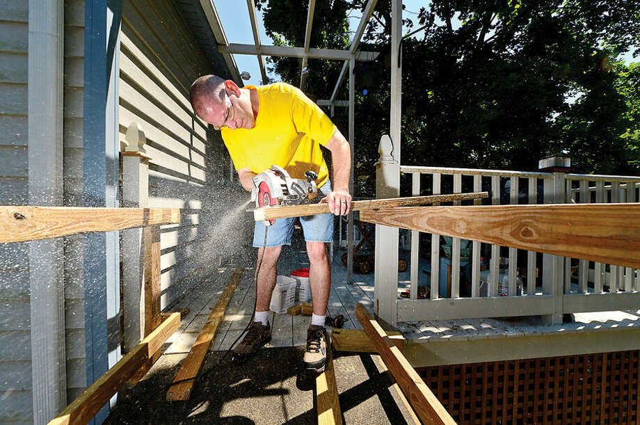 Hour photo / Erik Trautmann Local volunteers including Mark Hankla build an outdoor elevator at the home of veteran David Cole who fell ill last year and is now confined to a wheelchair.