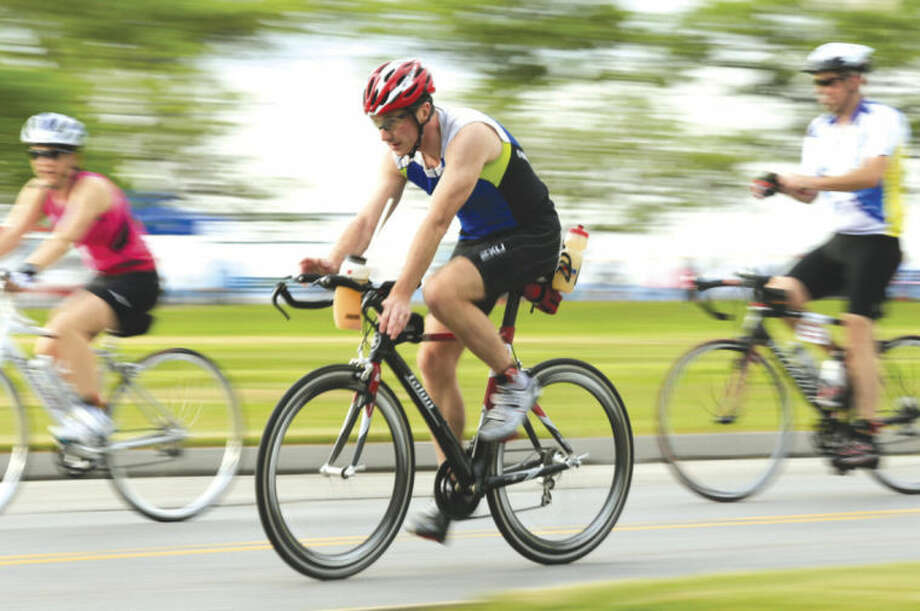 Photo by Chris Palermo.Ken Tulloch of Cos Cos, center, begins the bike portion of the Navigators Stamford KIC IT Triathlon Sunday morning at Cummings Beach.
