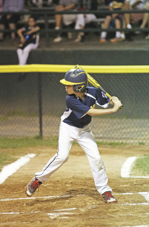 Hour photo/Danielle CallowayWeston's Andrew Amato is about to get a base hit during the District 1 championship game against Stamford North on Friday evening at Springdale Field in Stamford.