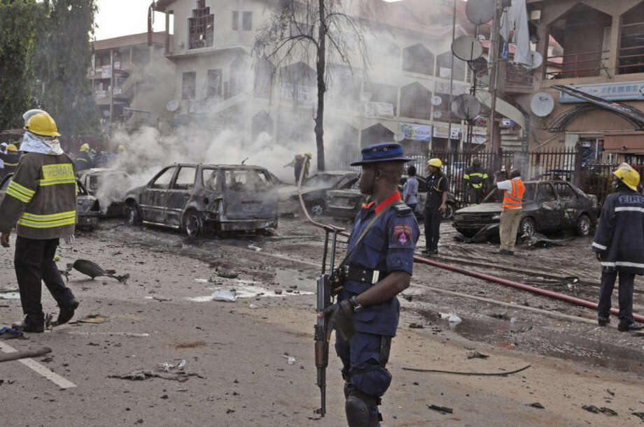 Rescue services work at the scene of an explosion, in Abuja, Nigeria, Wednesday, June 25, 2014. An explosion rocked a shopping mall in Nigeria's capital, Abuja, on Wednesday and police say at least over 20 people have been killed and many wounded. Witnesses say body parts were scattered around the exit to Emab Plaza, in the upscale Wuse 11 suburb. (AP Photo/Olamikan Gbemiga)