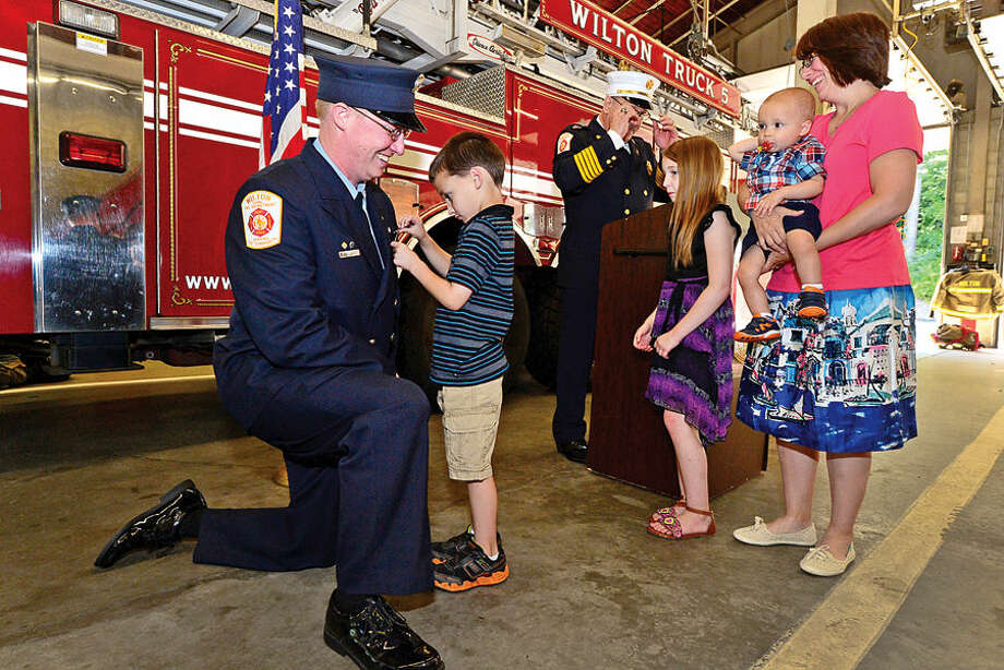Hour photo / Erik Trautmann Wilton firefighter Brian Elliott is pinned with his shield by his son Jackson, 6, while his family looks on including wife, Renee, daughter Abigail and infant son, Jacob, after being promoted to lieutenant during a brief ceremony at Fire Headquarters Thursday morning.