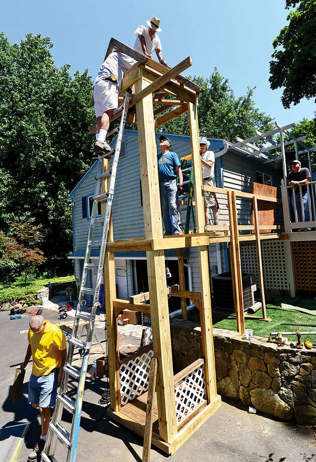 Hour photo / Erik Trautmann Local volunteers build an outdoor elevator at the home of veteran David Cole who fell ill last year and is now confined to a wheelchair.