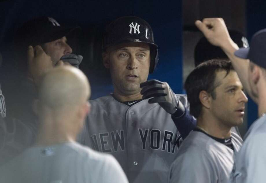 New York Yankees' Derek Jeter celebrates his solo home run with teammates in the sixth inning of MLB baseball action against the Toronto Blue Jays in Toronto on Tuesday, June 24, 2014. (AP Photo/The Canadian Press, Darren Calabrese)
