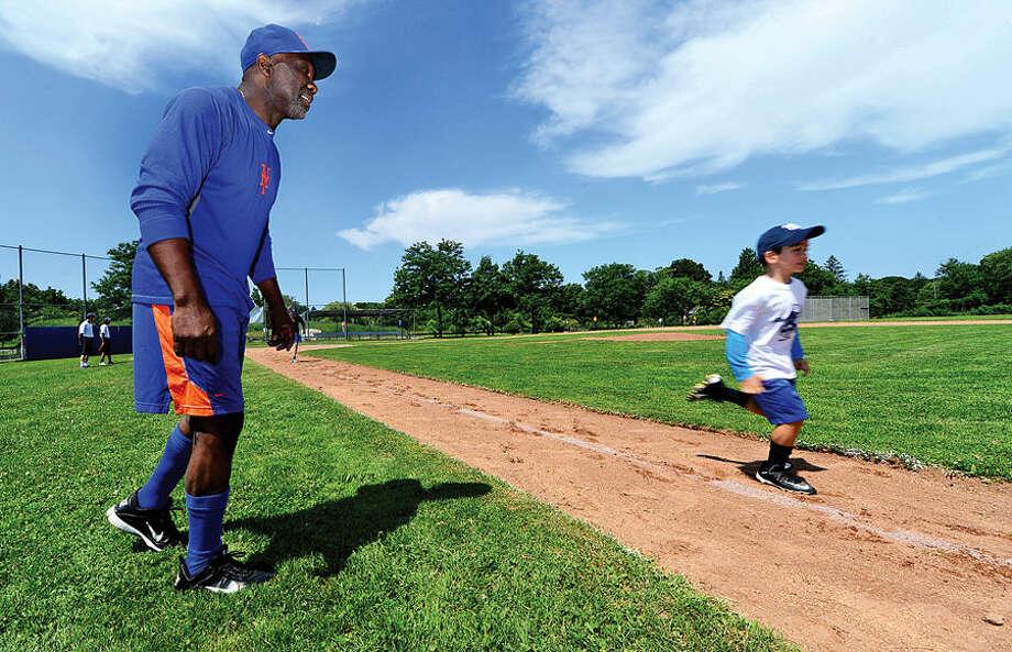Hour photo / Erik Trautmann Former Mets' major league baseball player, Mookie Wilson, instructs Baseball World campers on proper base-running technique Thursday morning.