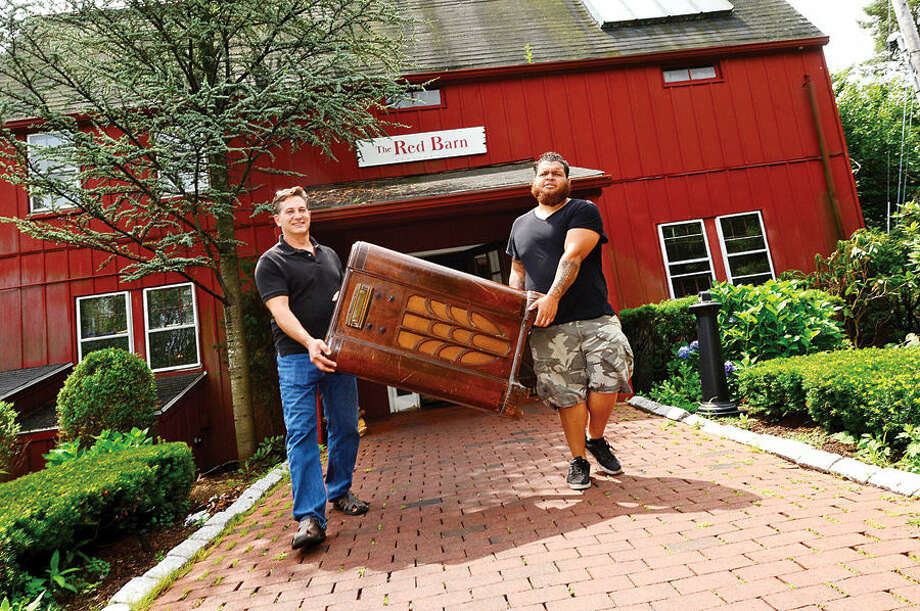 Hour photo / Erik Trautmann Ben Dacounto is helped outside with the antique GE cabinet radio he puchased by Simply Estated employee Manny Peppers as the historic Red Barn Restaurant in Westport holds a liquidation sale Saturday.